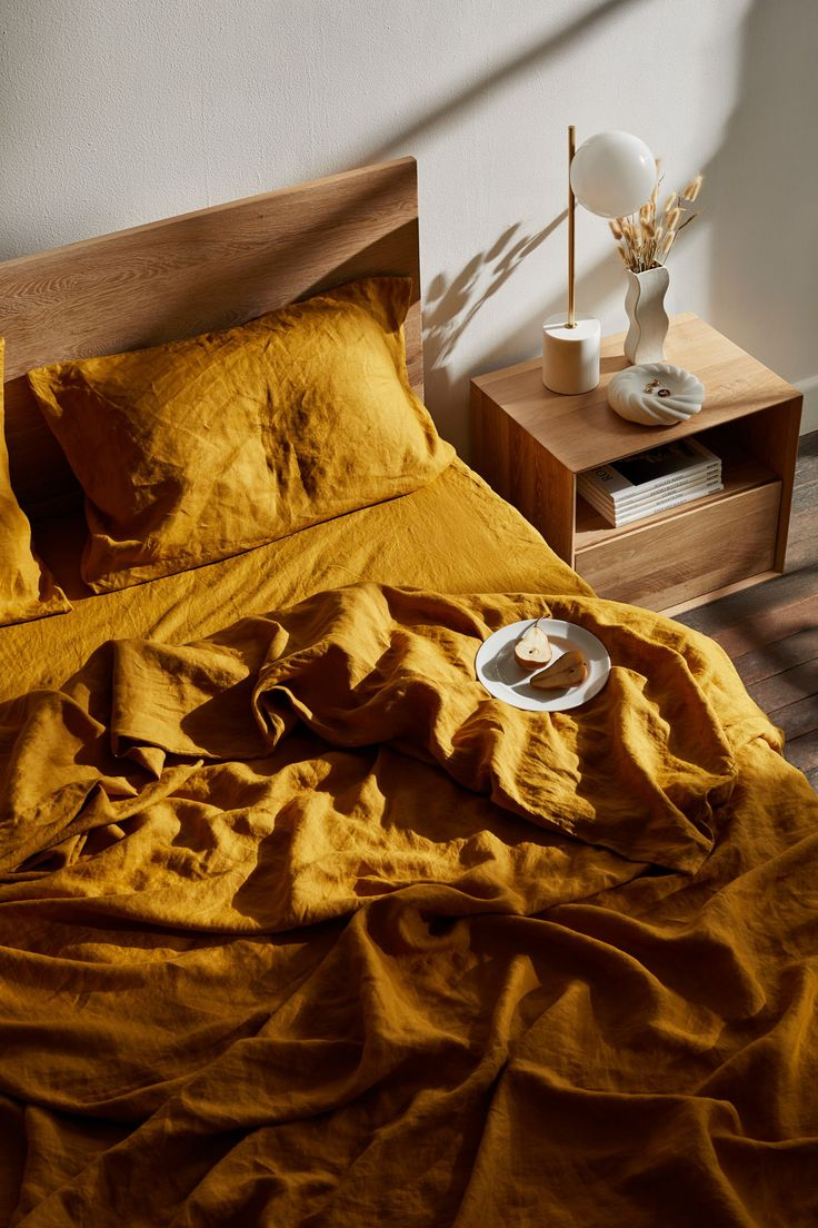 Add sunshine and warmth to your bedroom with our golden Turmeric linen sheets. Here they are styled beautifully with a minimal bedside table, geometric table lamp and ceramic vase with dried flowers.