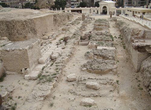 The archaeological site of the Serapeum in Alexandria in Egypt. Palimpsests originating here and in the Library of the Temple of the Muses may tells us more about ancient theatrical practices that may link the Karagiozis and Hadjiavatis characters to Ancient New Comedy.