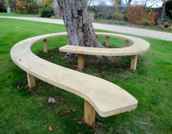Large swirling curved bench surrounds a tree. Unlike traditional tree surrounding benches, the tree can never outgrow this one.