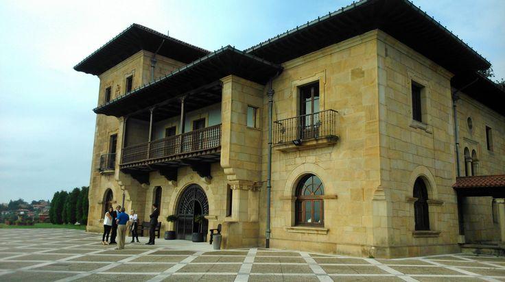 El Palacio de la Riega fue obra de Manuel del Busto, construido en 1919. El estilo dominante es el regionalismo montañés. Proyectado en un alto emplazamiento, posee casi 7 hectáreas donde la casona y la capilla anexa se alzan sobre una plataforma. Está rodeado de un bosque de eucaliptos