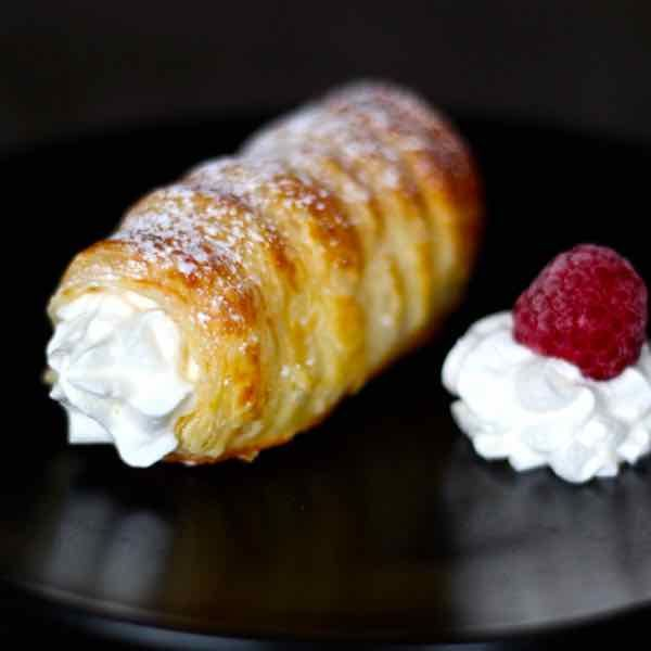 Kremrole is a deliciously crispy roll-shaped puff pastry that is filled with meringue or whipped cream that is popular in the Czech Republic, Austria, Germany and Slovakia.