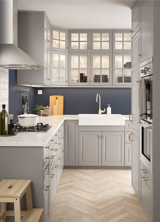 L-shaped kitchen with traditional wall and base cabinets with grey doors and glass doors.