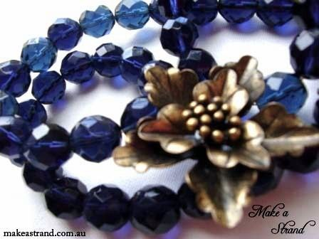 Deep, rich blue faceted short necklace with a brass flower pendant designed to sit at the throat and matching brass metal clasp In stock: AU$75 + postage