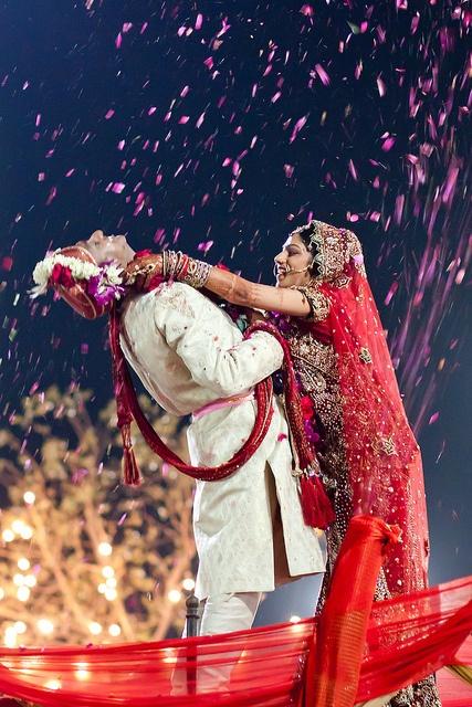 Indian Wedding : Ceremony- The bride puts the orchid flower garland around bridegroom's neck