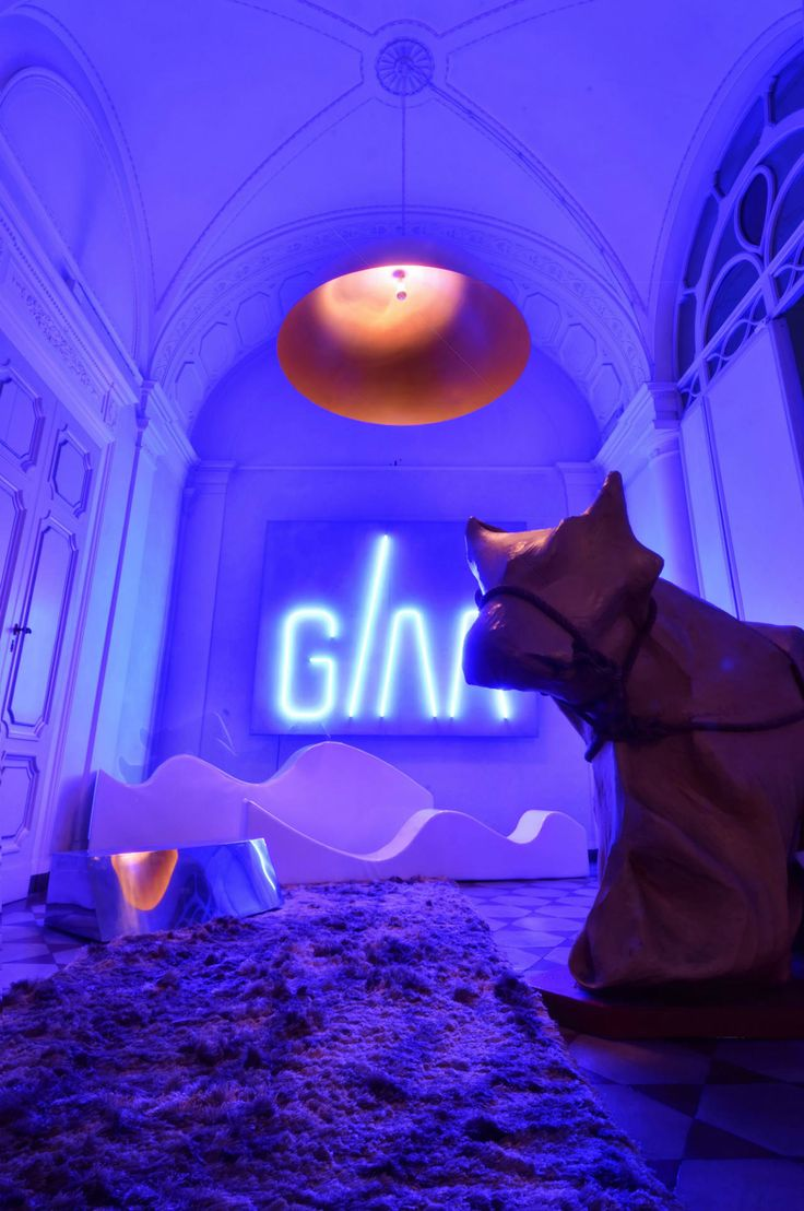 "Having crossed the threshold, your attention is captured be the GAA sign made from blue neon glass tubes, and by ""Pac Cow"", a work by the artist Ugo Ziqqurat Zatini, depicting a cow covered in cardboard #interdema #designstudio #moderndesign #GiraldiAssociati #StudioGAA #современныйдизайн"