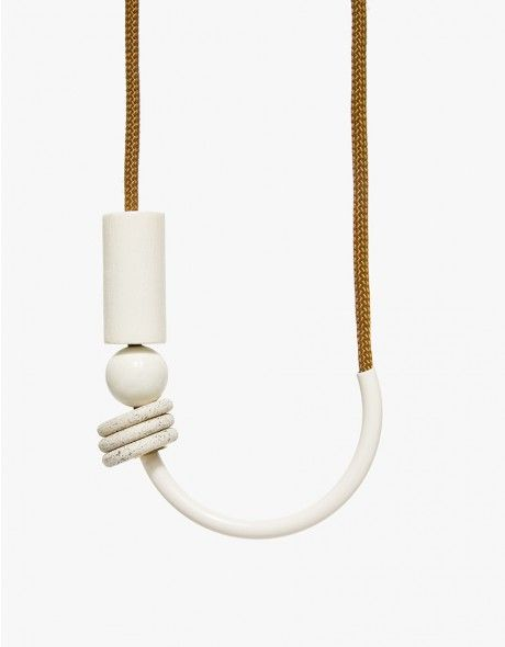 a minimalist white-coated brass curved bar necklace set on a vintage sienna cord with white-coated beads, brass and vintage ceramic beads