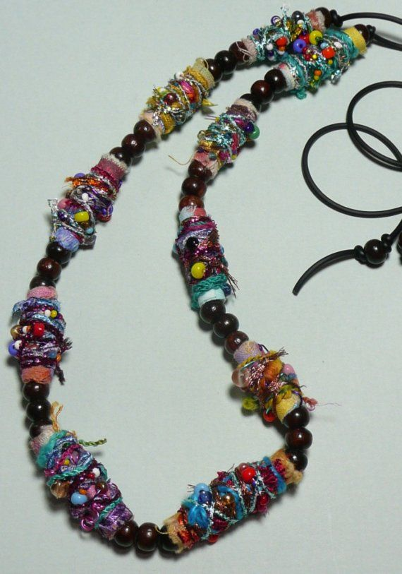 The beads in this piece are fabric that has been painted, torn into strips, wrapped and then embellished.They are strung on rubber cord with wooden beads.