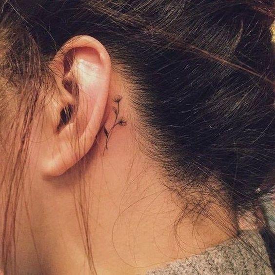 tatouage derrière l'oreille – une jeune femme avec un petit tatouage noir avec …   – Tattoo