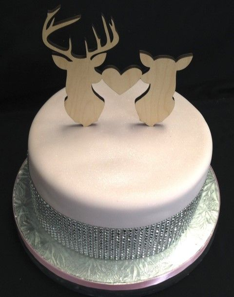 Simple pale pink cake with diamante ribbon and stag and deer wooden toppers.