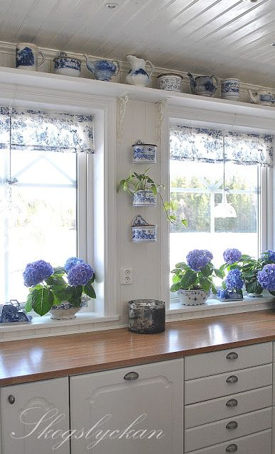 beautiful fresh white kitchen with blue hydrangeas and Delft china