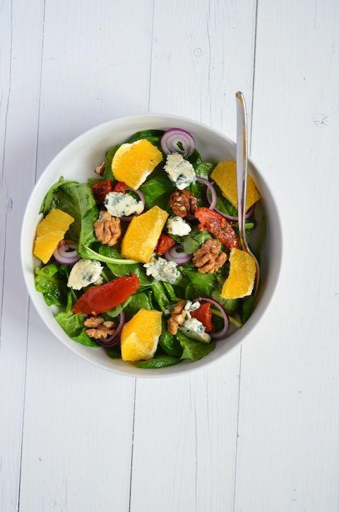 Zomersalade: Ingrediënten voor 4 personen 200 gr spinazie 2 sinaasappelen 1 rode ui 50 gr Roquefort 30 gr walnoten 80 gr zongedroogde tomaten 1 el olie Zwarte peper