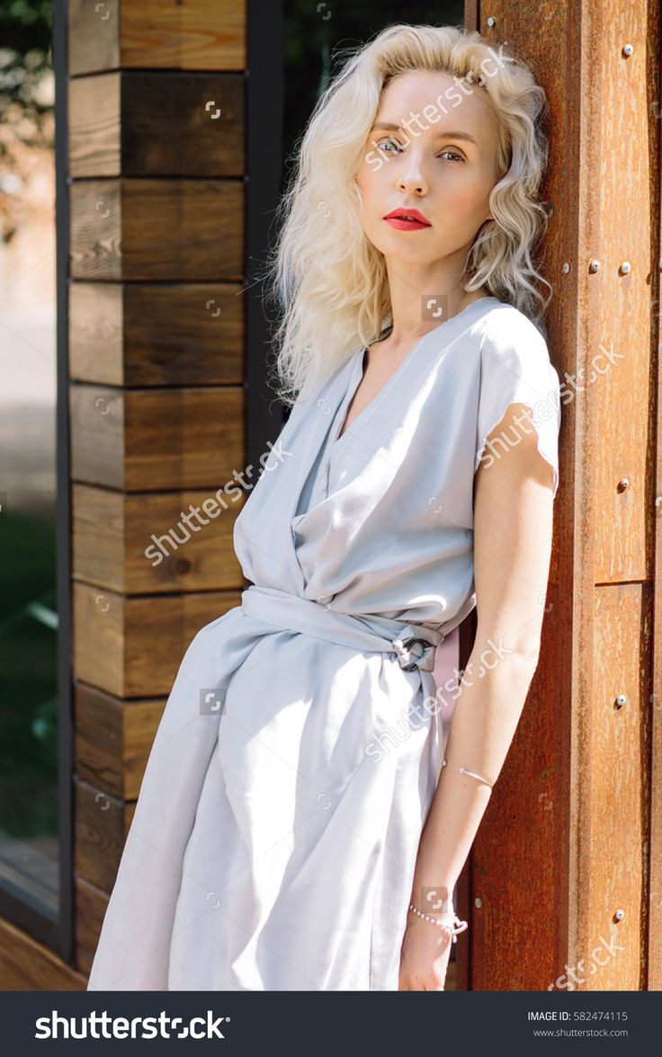 Portrait of young beautiful blonde woman in Asian style blue trendy dress posing outside in the city streets. Lonely girl standing next to wooden building. Close up. Fashion concept. Natural beauty