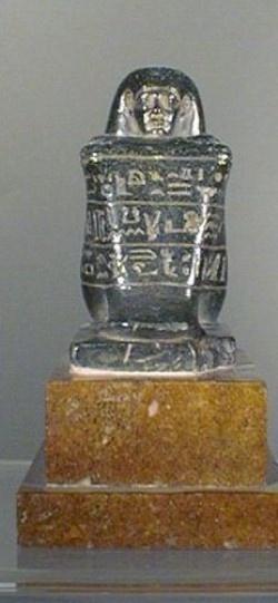 Estatua Cubo de Hor. III Per.Inter. XXII Din o Din.Libia. El Cairo, Museo Egipcio. Masa de granito negro, totalmente grabado con imagenes divinas e incripciones, sobresale tan sólo la cabeza y someramente los brazos, evocando los modelos del reino nuevo.