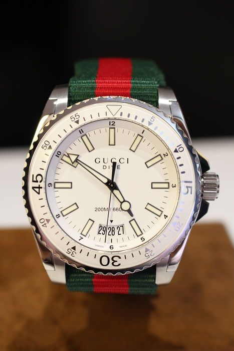 Gucci - Heren duikhorloge  Gucci DIVE YA136207 Analog men's watch Steel case green and red nylon strap (adjustable) steel folding clasp Saphire glass White dial 20ATM waterresistant 45mm diam case New 2 years warranty 22cm total length Original box and papers Registered shipping  EUR 46.00  Meer informatie