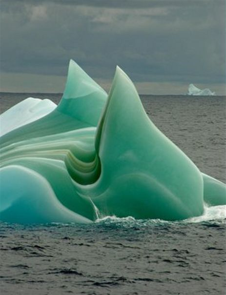 Jade Iceberg, Antarctica. When seawater at depths of more than 1,200 feet freezes to the underside of massive ice shelves, it forms 'marine ice.' Enormous hunks of ice break off from the ice shelf, creating icebergs. When one of these icebergs overturns, its jade underside is revealed. The wondrous color of this 'marine ice' results from organic matter dissolved in the seawater at those great depths. Green icebergs are infrequently seen because their verdant bellies are underwater