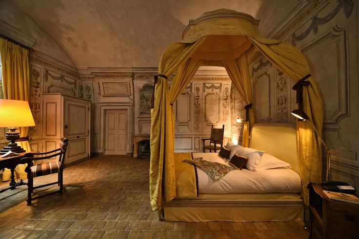A heavily mural decorated bedroom suite with a beautiful gold damasck antique canopy bed, in a restored French château in Beaujolais. Hotel and resort photography by Kent Johnson.