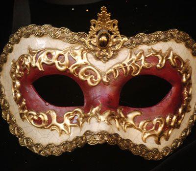 Maschera realizzata interamente a mano in cartapesta.  Decorata con stucco, foglia d'oro ed impreziositasul contorno della maschera con macramè.