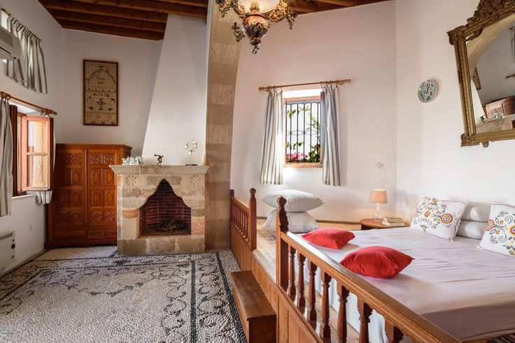 Bedroom with fireplace and traditional Lindian bed #Lindos #Rhodes #LindianCollection #Seaviews #VillaMeandros