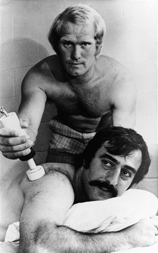 Pittsburgh Steelers quarterback Terry Bradshaw applies a muscle relaxer to number two signal caller Terry Hanratty at the club's training camp at St. Vincent College in Latrobe, Pa., July 19, 1973. Bradshaw and Hanratty battled for the regular quarterbacking job three years ago, and now Bradshaw is fighting to improve his passing game.