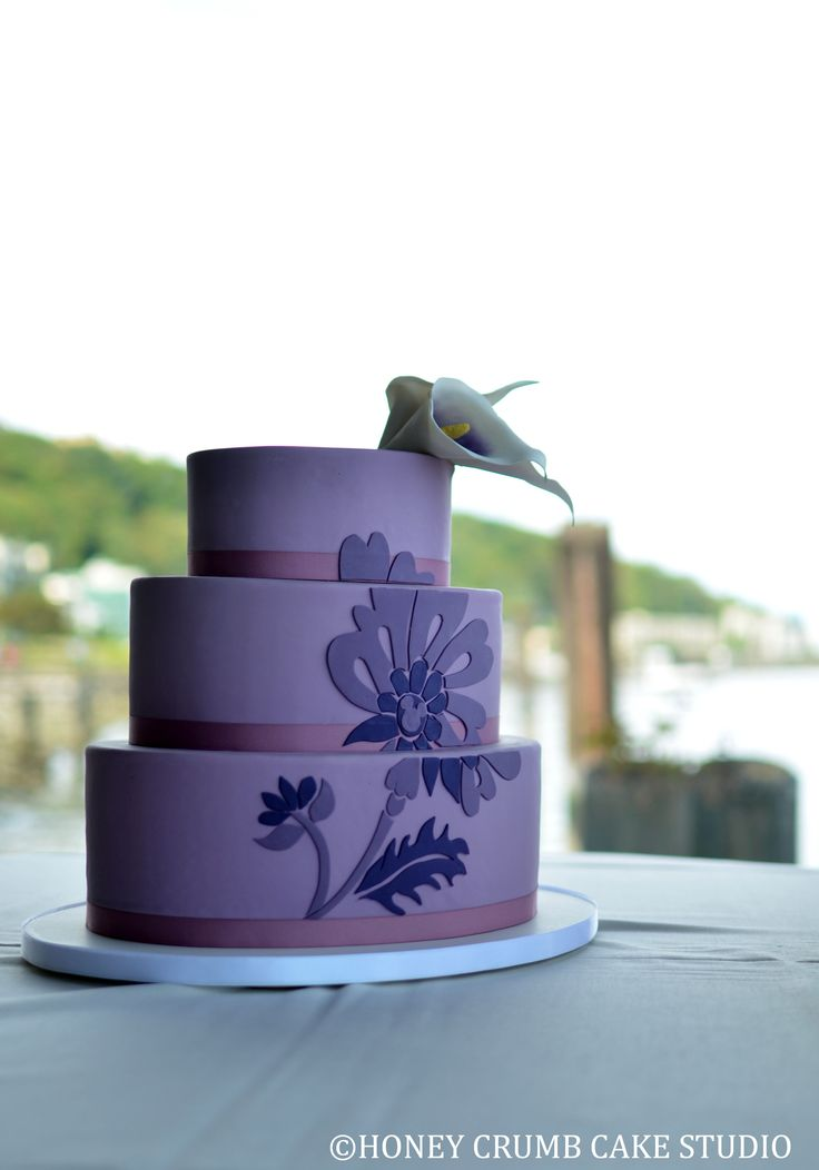 Three-tiered oval wedding cake in lavender-tinted fondant, with custom handcut gumpaste applique design and handcrafted sugar Calla lilies.