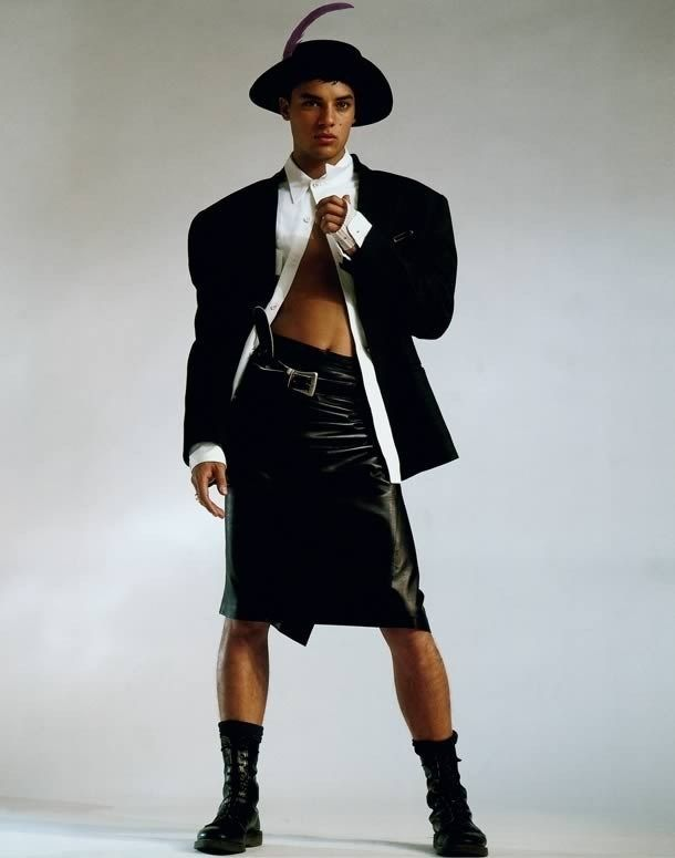 """""""To me, this is quintessential Ray Petri styling. It's got the tough stance from the model, which is a very sexy, cool stance. He's wearing a leather skirt which is a woman's item of clothing, we have the sexy midriff, strong arms, a touch of vulnerability and a porkpie hat, we're mixing it all. Is he sexy, is he strong, is it aggressive? The vulnerability and strength of a guy and giving a man the same status as a woman."""""""