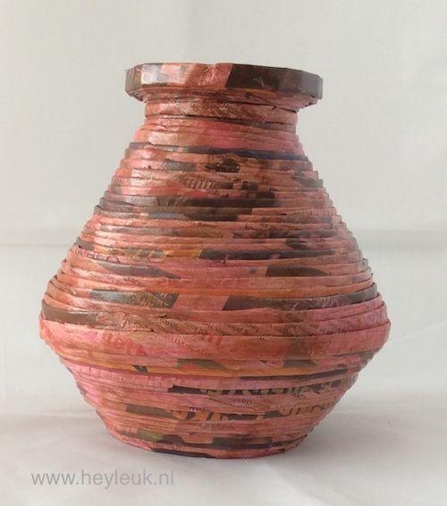 Een mooie vaas met een dikke buik die gemaakt is van gerolde papierstroken. De vaas loopt van smal naar breed en omhoog wordt hij opnieuw smaller.