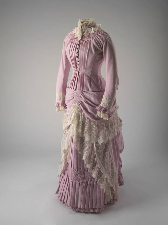Pink wool bodice and skirt c. 1883 - 1886. Side view. This dress belonged to one of the daughters of William Pitt Faithfull, most likely his youngest daughter, Lilian.The tight fitting, boned bodice and bustled skirt decorated with lace flounces and frills are of the style fashionable among the middle and upper classes in Britain and Europe during this period.Woollen Dress from the Springfield station, NSW, purchased from the David Jones department store in Sydney
