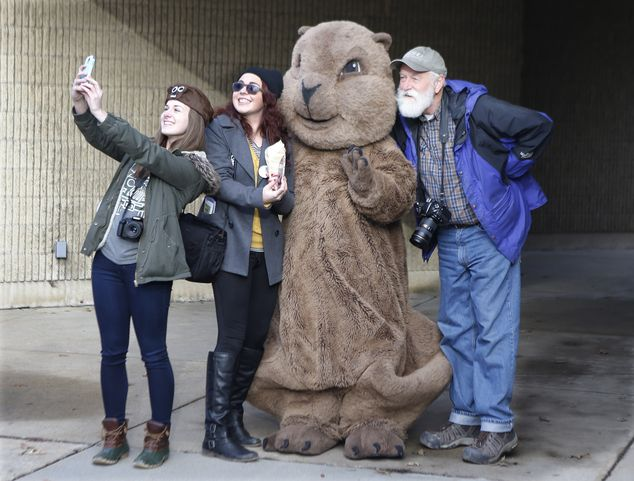 A group of visitors pose for pictures and take selfies with the 'Punxsutawney Phil' mascot outside the public library in Punxsutawney, Pennsylvania on Monday