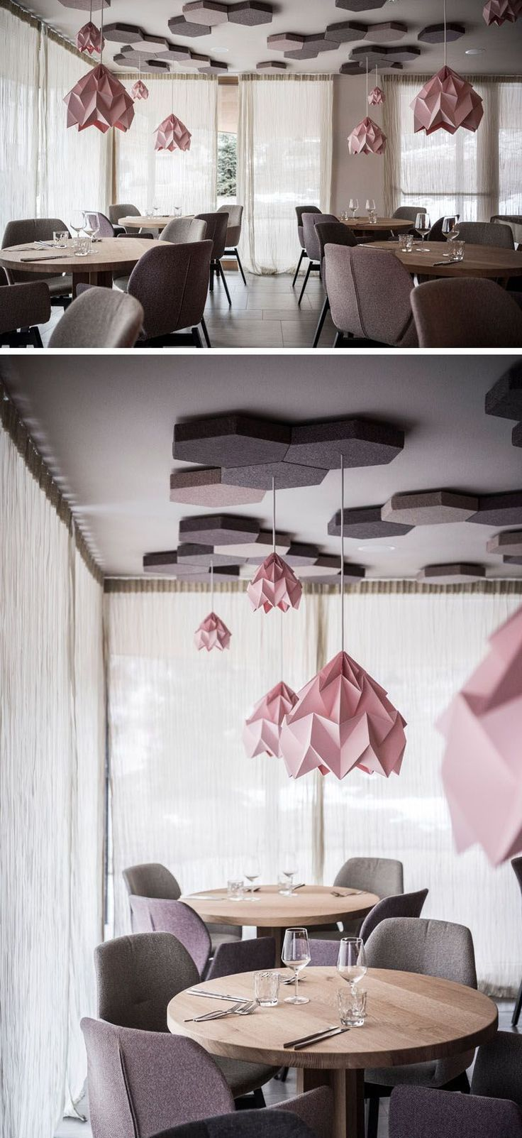 The contemporary pink light fixtures hanging from honeycomb details are the focal point in this modern hotel restaurant. Round wood tables, with dusty pink and gray wool upholstered chairs help to create a cozy atmosphere.