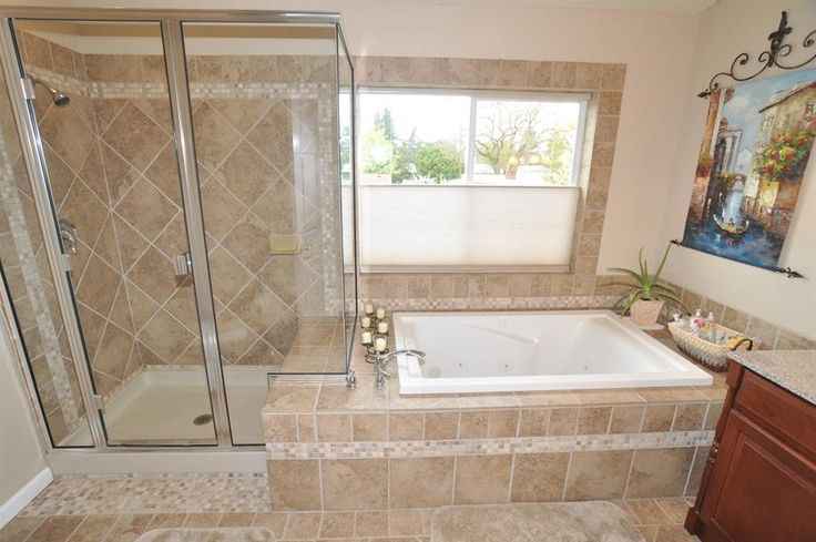 5-piece master bath with extensive tilework. Jetted tub with tile surround. Tile surround in large shower with glass enclosure.