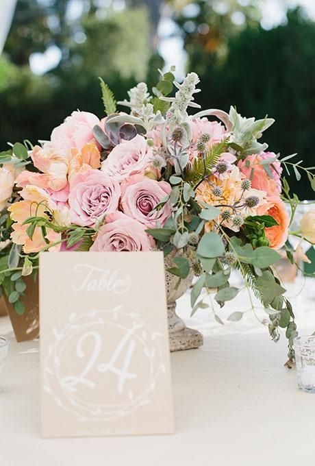 A rustic kraft paper table number with white writing | Brides.com