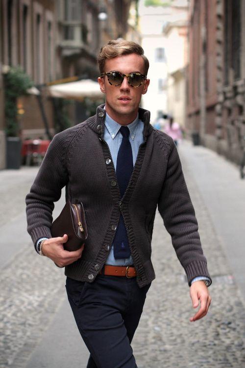 Den Look kaufen: https://lookastic.de/herrenmode/wie-kombinieren/strickjacke-langarmhemd-chinohose-krawatte-guertel/421   — Dunkelblaue Chinohose  — Brauner Ledergürtel  — Dunkelblaue Krawatte  — Blaues Chambray Langarmhemd  — Dunkelgraue Strickjacke