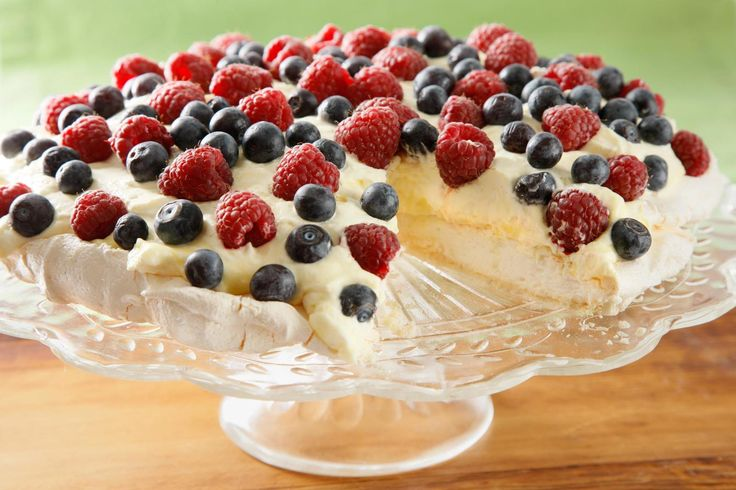 This pavlova recipe, a meringue cake with a crunchy exterior and marshmallowlike interior, is topped with a lemon curd whipped cream and berries.