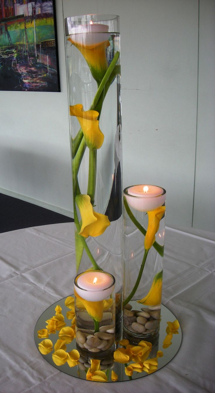 Stunning Yellow Calla Lily Center Pieces. I would add white rocks on the bottom and have a blue table clothes.