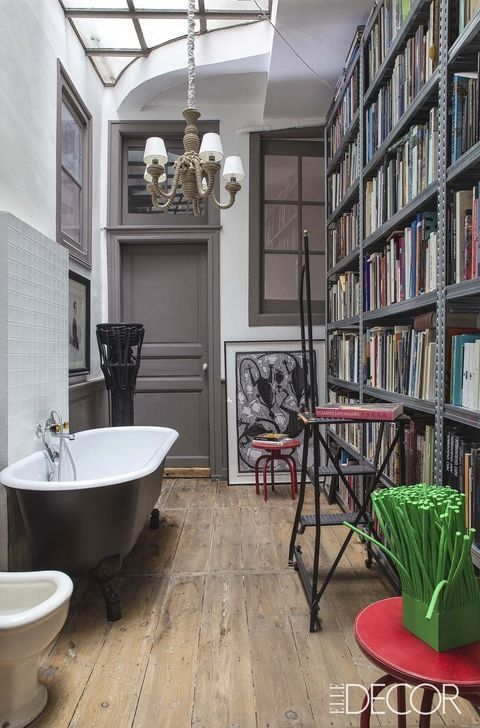 This highly-curated French duplex apartment is like an interactive art museum. In the master bath, floor-to-ceiling galvanized-iron bookshelves are reached with a metal library ladder; the sculptures and paintings are by Astuguevieille.