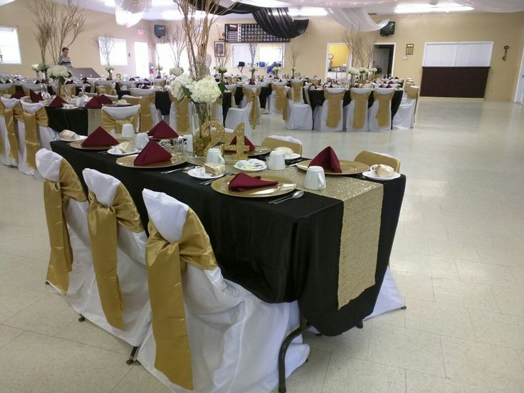 Antique gold sashes, white chair covers, black satin table cloth, gold sequence runner, gold charger plates, Marcella napkins and vases with rocks gold branches and hydrangeas. Also gold glitter numbers and Mercury glass tea light votives!