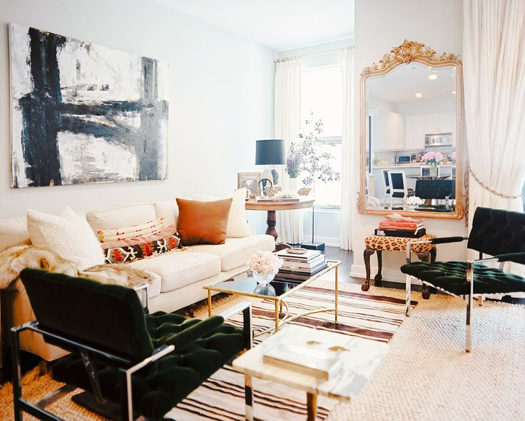 White walls, white couch, green chairs, white pillows, tan pillows, faux fur throw blanket, black and white wall art, large gold framed mirror, striped rug, and gold coffee table