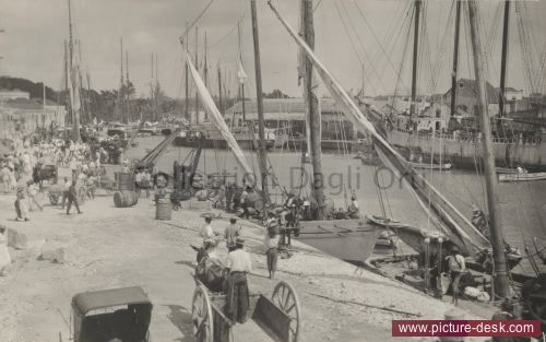 Bridgetown's waterfront is crowded with people and lined with boats. Bridgetown, Barbados Island (Date: 1/1/1921)