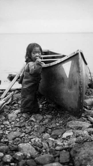 Inuit child with a canoe / Enfant inuit à côté d'un canot   by BiblioArchives / LibraryArchives