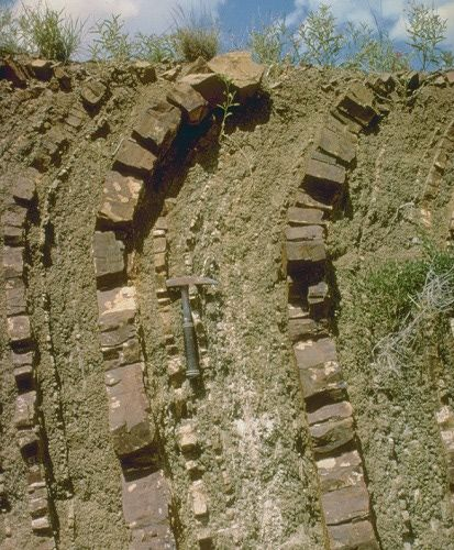 Soil creep moves the fractured rock of the Hammond Formation down slope near Marathon, Texas. Creep is faster nearer the surface. The rock is not actually bent.