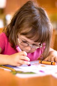 Child drawing a picture with crayons