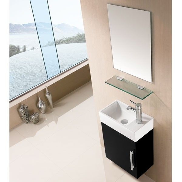 Idéal pour les petites salle de bain, ce meuble noir est à mi-chemin entre le meuble simple vasque et le lave-mains. Il est accompagné d'une tablette en verre et d'un miroir rectangulaire. #meubles #salledebain #design
