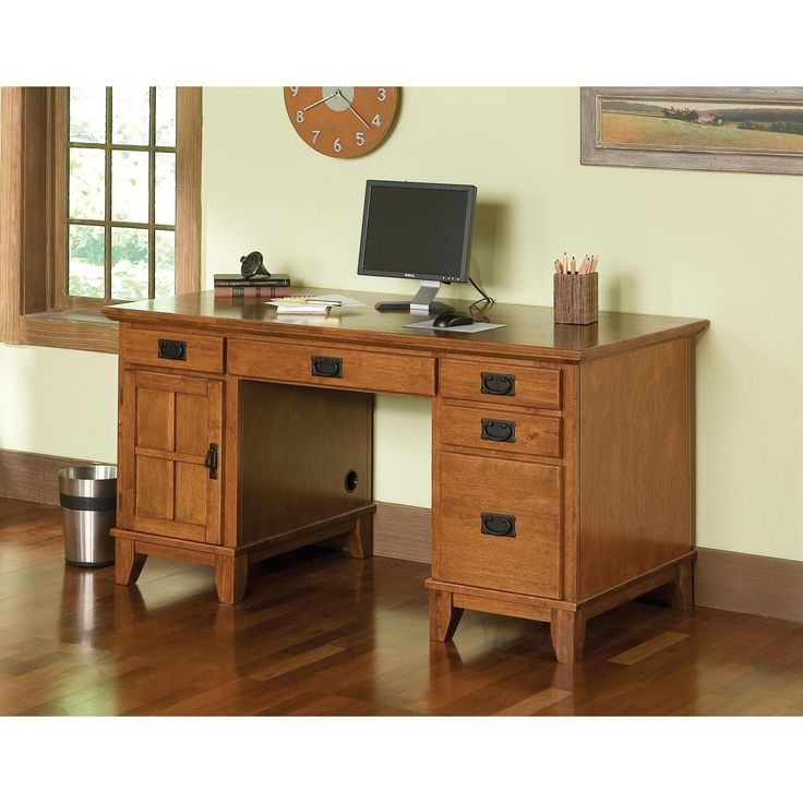 Enhance the decor of your home or office with this oak pedestal desk. Constructed of solid hardwood and featuring a rich oak finish, this desk offers a center drop-down drawer for easy keyboard use and four glide drawers for convenient storage.
