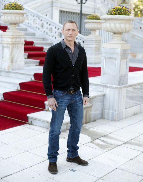 Smart casual look. Daniel Craig - Grey shirt, black cardigan, blue jeans, brown suede chukka boots.