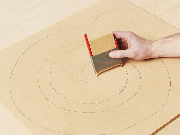 Paso 1: Confeccione la «guía de dibujo», que le permitirá dibujar dos líneas paralelas con la forma del cuerpo de la serpiente en el interior de un círculo de 50 cm. Para realizar la guía de dibujo utilice una pieza de madera de 7,5 cm de ancho x 10 cm de largo, coloque un lápiz en cada extremo y sujételo con cinta adhesiva. Luego dibuje el cuerpo de la serpiente enrollada en el interior del círculo. Cree la cabeza y la cola dibujándolas a mano alzada.