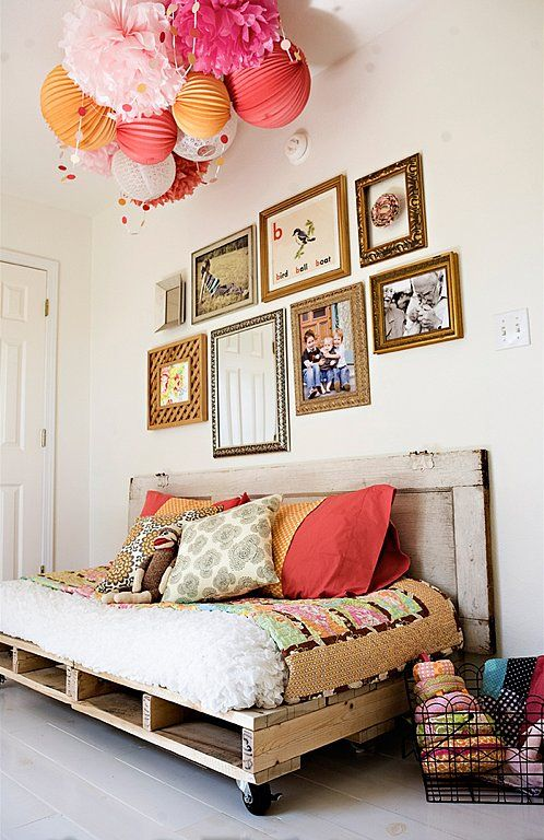 Doesn't this pallet daybed look stunning? The mismatched pillows, gallery wall, and paper pom-poms add a nice touch. Source: Under the Sycamore