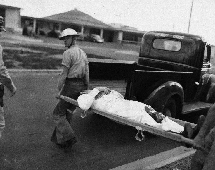 0-G-77625: U.S. Navy sailor injured during Japanese Attack on Pearl Harbor, Territory of Hawaii, being carried to safety, December 7, 1941. Location: Naval Air Station, Kaneohe Bay, Oahu.