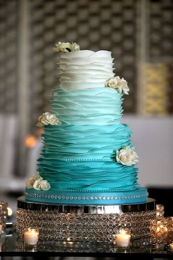 Some colors are easy to incorporate on your wedding cake, such as blush or lavender. But bolder hues often prove to be more difficult to keep the same color saturation and still look sophisticated. This teal ombre wedding  cake with white flowers is a really lovely example of how you don't have to sacrifice elegance when working with bold colors.