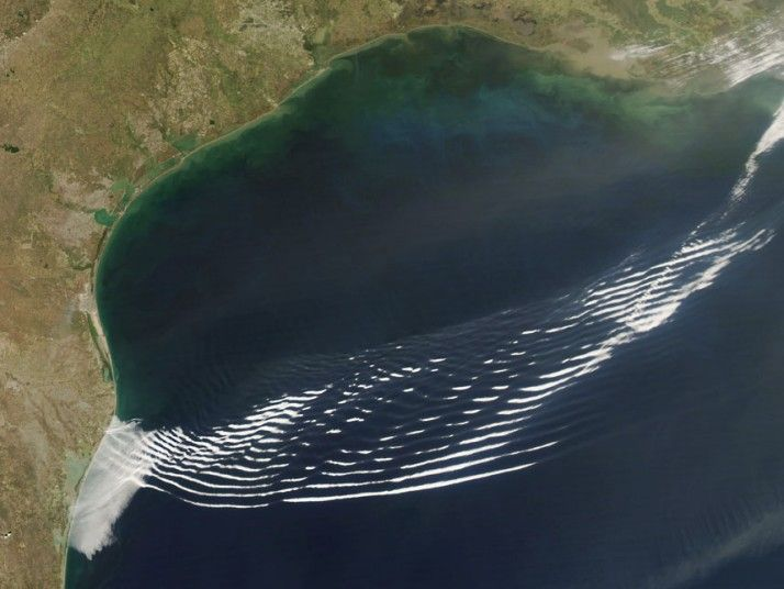 Gravity wave clouds over the Gulf of Mexico, Texas, US.  Gravity clouds are distinctive ripple-like clouds that usually form over the ocean. The ripples are caused by the movement of a high pressure area and its cold front. Dense air is pushed upwards into the less dense air above it, forming the crest of the wave. Gravity pulls the dense air back down, forming the trough. This image was taken by the Moderate Resolution Imaging Spectroradiometer (MODIS) instrument on NASA's Aqua satellite.
