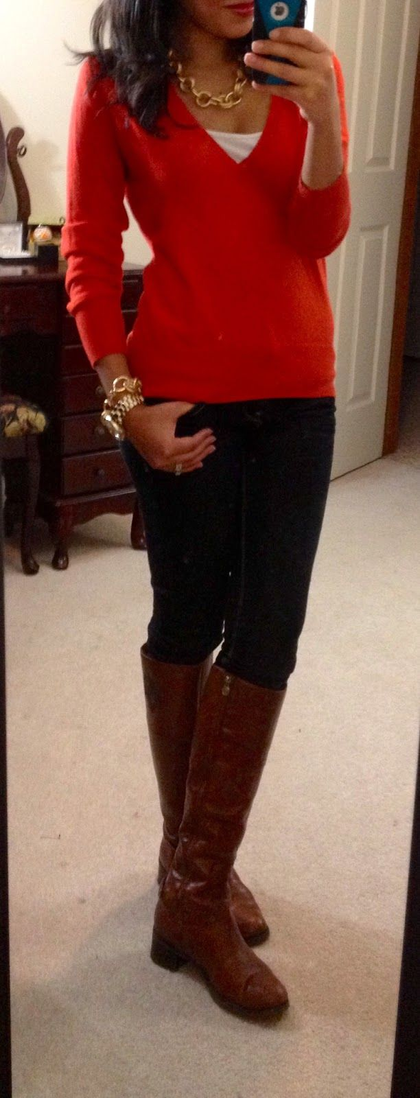 orange sweater with dark wash jeans and brown leather boots